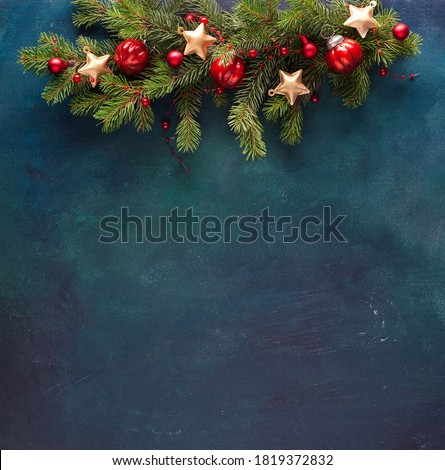 Fir branch with Christmas decoration on a dark blue-green painted wooden background. Flat lay.  New Year background with place for text.