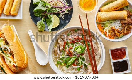 assorted vietnamese dishes with pho, bahn mi, spring rolls in top down composition on dinner table Royalty-Free Stock Photo #1819377884