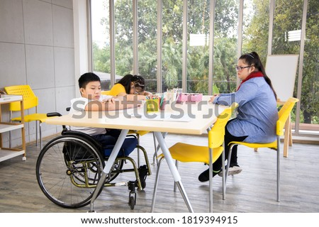 Two girls with Down's syndrome and disabled boy on wheelchair sit in classroom and wait for their teacher.  Royalty-Free Stock Photo #1819394915