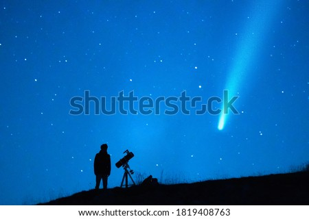 Astronomy lover with a telescope observing a comet in the blue starry sky at night. Silhouette of a person observing the immensity of the universe and the stars. Trace of a comet or a shooting star. Royalty-Free Stock Photo #1819408763