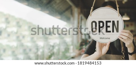 Panoramic banner. friendly waitress woman turning Open sign board reopen after coronavirus quarantine is over in cafe coffee shop ready to service, restaurant, take away, food and drink concept