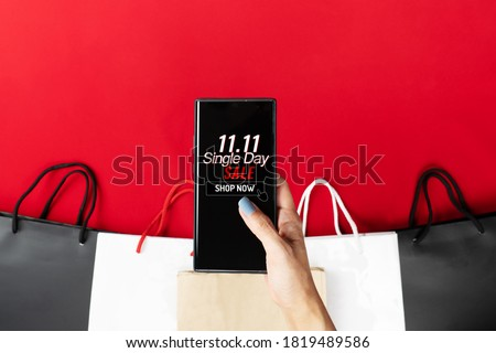 woman hand holding smartphone with shopping bag, China 11.11 single day sale concept Royalty-Free Stock Photo #1819489586