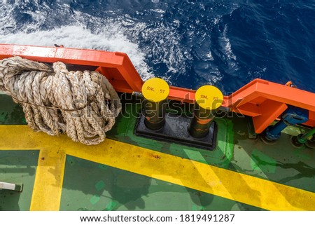 Hawser mooring line stored next to mooring bitts at foward deck of a tug boat Royalty-Free Stock Photo #1819491287