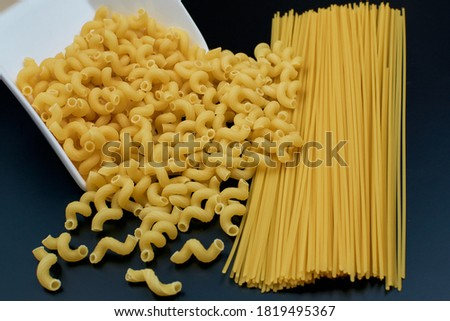 Small spring-shaped pasta is poured out of a white saucer. Spaghetti pasta on a dark background. close-up