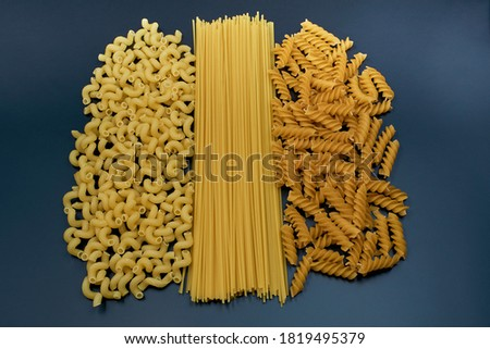 Mix of pasta on a dark background. Three varieties of pasta. Spaghetti pasta and two different varieties of spiral pasta