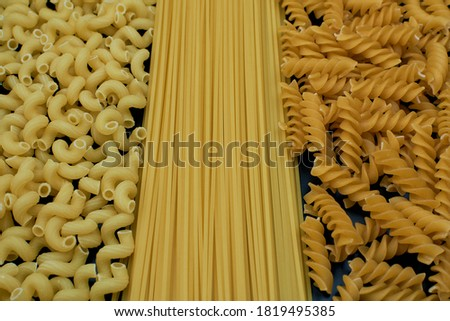 Pasta mix close-up. Three varieties of pasta. Spaghetti pasta and two different varieties of spiral pasta