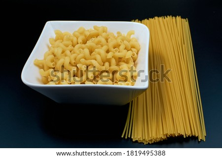 Small pasta in the shape of a spring in a white plate Spaghetti pasta on a dark background. side view.