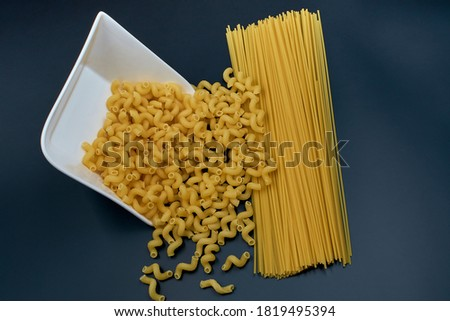 Small spring-shaped pasta is poured out of a white saucer. Spaghetti pasta on a dark background