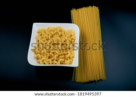 Small pasta in the shape of a spring in a white plate Spaghetti pasta on a dark background. top view.