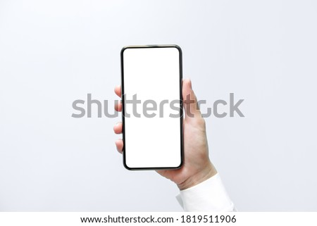 Smartphone mockup. Close up hand holding black phone white screen. Isolated on white background. Mobile phone frameless design concept.