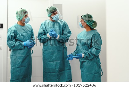 Doctors wearing ppe equipment face surgical mask and visor fighting against corona virus outbreak - Health care and medical workers concept  Royalty-Free Stock Photo #1819522436