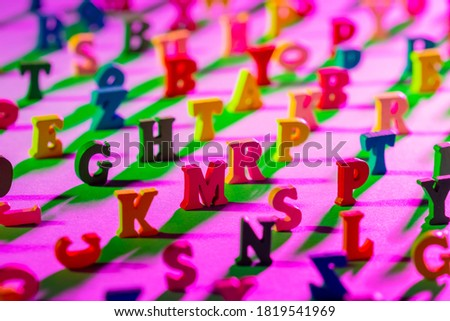Letters of alphabet are arranged chaotically. 3D letters cast a shadow on table. Multicolored symbols of English language. Characters around edges of frame are out of focus. ABC letters top view.