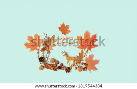 happy autumn. composition with leaves, nuts, deer toy on blue background. fall time concept. thanksgiving and halloween holiday. flat lay