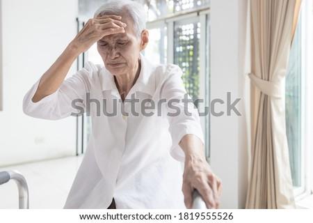 Exhausted asian senior woman is touching her head with hand,symptoms of vertigo illness,loss balance dizzy,meniere's disease,feel unwell faint,sick elderly people having a  headache,health problem