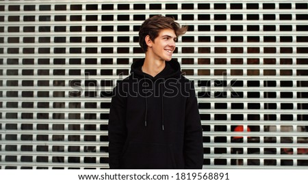 City portrait of handsome young guy wearing black blank hoodie or sweatshirt with space for your logo or design. Mockup for print