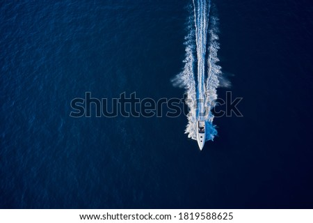 Large speed boat moving at high speed. Top view of a white boat sailing to the blue sea. Drone view of a boat sailing. Motor boat in the sea. Travel - image. Royalty-Free Stock Photo #1819588625