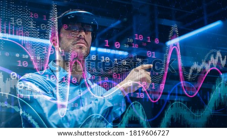 Caucasian Male IT Specialist and Businessman Wearing Futuristic VR Helmet and Working with Digital Data. Concept Shot of High Speed Internet Visualization and Graph Statistics in Foreground Royalty-Free Stock Photo #1819606727