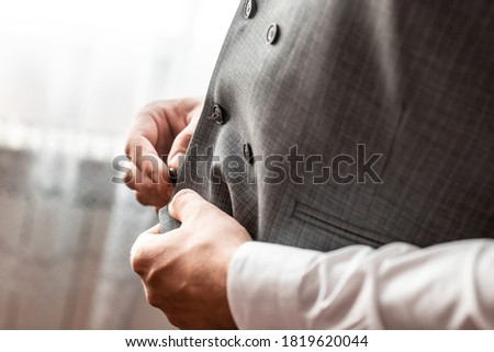 groom fastens a button on his vest at the groom's morning gatherings.the groom fastens the button. wedding day. gray jacket. hands of the groom, Grooms morning preparation. #1819620044
