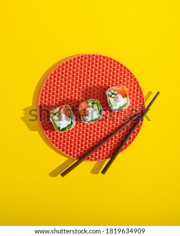 Sushi roll top view on creative orange plate with chopsticks on yellow background isolated