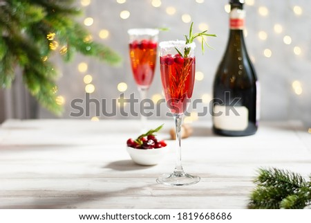 Mimosa festive drink for Christmas - champagne red cocktail Mimosa with cranberry for Christmas party, copy space and fir tree branches #1819668686