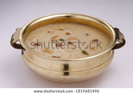Indian sweet dish Palada Payasam or Kheer, Indian main sweet dish made using ada, milk , sugar and dry nuts _Arranged in kerala traditional way in brass vessel with white background