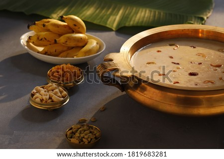 Indian sweet dish Palada Payasam or Kheer,Indian main sweet dish made using ada,milk,sugar and dry nuts _Arranged in kerala traditional way in brass vessel with grey background,selective focus
