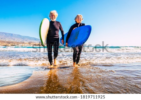 two old and mature people having fun and enjoying their vacations outdoors at the beach wearing wetsuits and holding a surfboard to go surfing in the water with waves - active senior smiling  Royalty-Free Stock Photo #1819711925
