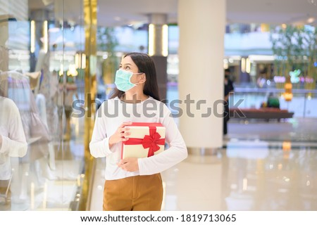 A woman wearing protective mask holding a gift box in shopping mall, shopping under Covid-19 pandemic, thanksgiving and Christmas concept. #1819713065