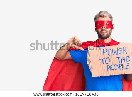 Young blond man wearing super hero custome holding power to the people cardboard banner with angry face, negative sign showing dislike with thumbs down, rejection concept