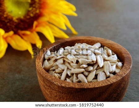 Sunflower Seed Kernels In Wooden Bowl.  Sunflower in background.  Shallow depth of field with horizontal composition. Royalty-Free Stock Photo #1819752440