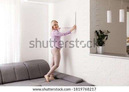 woman holds photo canvas at home