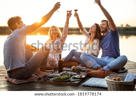 Group of friends having fun on picnic near a lake, sitting on pier eating and drinking wine. Royalty-Free Stock Photo #1819778174
