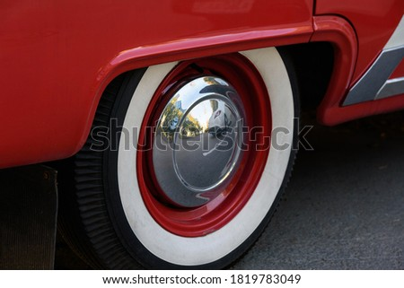 Closeup photo of the rear wheel of a magnificent retro car. The wheel has a red stamped disc in the body color, a large chrome hood and white wall.