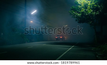 Classic car drive into abandoned road with large group of smoke and ghost town concept Royalty-Free Stock Photo #1819789961