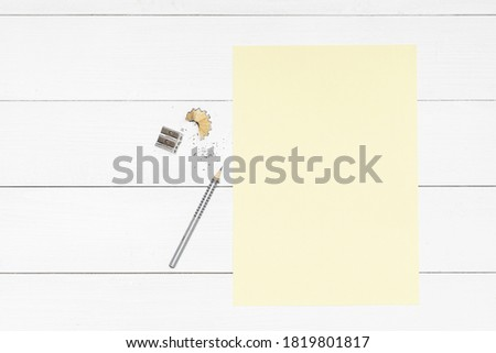 a pencil, a pencil sharpener and a yellow sheet of paper on a white wooden table