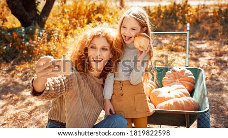 Happy young adult mother and little daughter having fun and spending autumn day together. Smiling woman making selfie on modern smartphone while her charming child holding pumpkin in hands