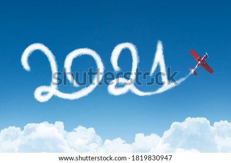 Happy New year 2021 concept on the background below cloudscape. Drawing by passenger airplane white vapor contrail in sky #1819830947