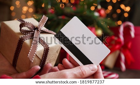 Young woman holding a credit card and a gift box against the background of Christmas decor and gifts, close-up. Christmas and New Year shopping on the Internet, payment by credit card. #1819877237