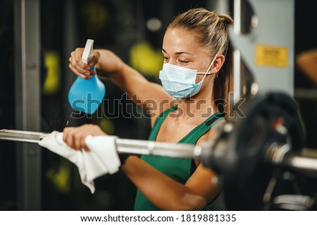 Shot of a muscular young woman with protective mask cleaning fitness gym equipment before workout during Covid-19 pandemic. Royalty-Free Stock Photo #1819881335