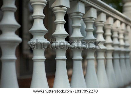Balusters in the decoration of the veranda railings. An architectural element made of wood. An old manor outside the city. Detail of a building from the last century. Royalty-Free Stock Photo #1819892270