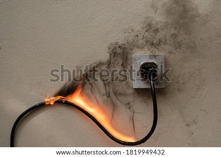On fire electric wire plug Receptacle on the concrete wall exposed concrete background with copy space #1819949432