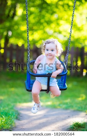 Happy laughing toddler girl with curly hair wearing a blue dress enjoying a swing ride on a sunny summer playground in a park #182000564
