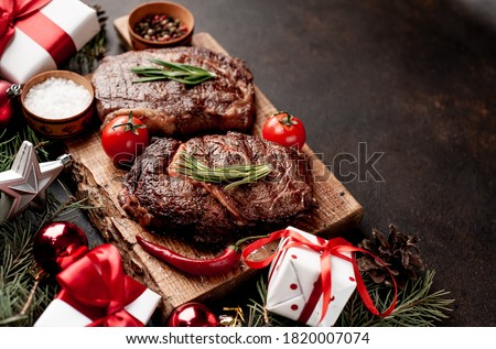 Christmas dinner for two, grilled beef steak, ribeye, greens and spices on a stone table with a Christmas tree and New Year's toys with copy space #1820007074