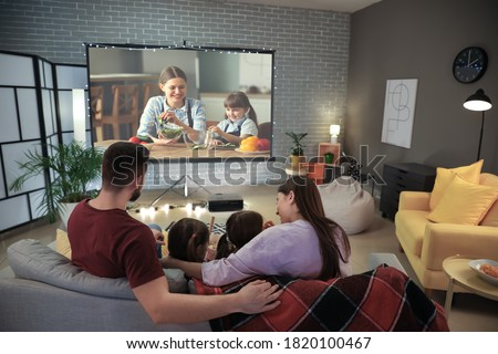 Young family watching movie at home Royalty-Free Stock Photo #1820100467