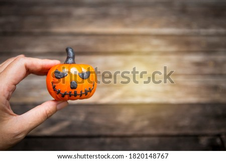 Funny Halloween pumpking in girl hand over blurred wood background with vintage warm light, happy halloween concept #1820148767