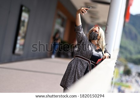Portrait of a middle aged woman in a fashion leopard pattern dress at the time of Corona Virus with protective surgical face mask making selfie photo with her phone outside a store. Alert Covid-19.