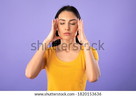 Concentration Concept. Portrait of young woman holding fingers on temples, thinking hard, trying to concentrate, isolated over purple studio background. Lady doing breathing yoga practice Royalty-Free Stock Photo #1820153636
