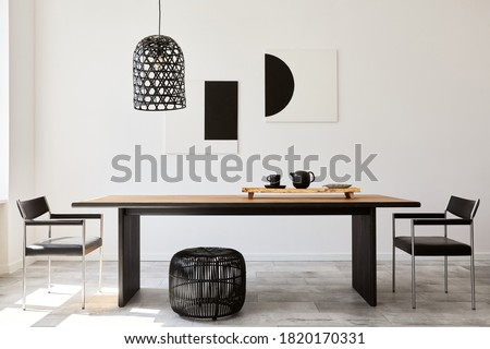 Stylish dining room interior with design wooden family table, black chairs, teapot with mug, mock up art paintings on the wall and elegant accessories in modern home decor. Template. Royalty-Free Stock Photo #1820170331