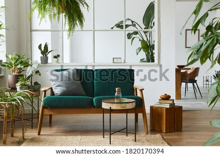Stylish scandinavian living room interior with green velvet sofa, coffee table, carpet, plants, furniture, elegant accessories in modern home decor. Template. Royalty-Free Stock Photo #1820170394