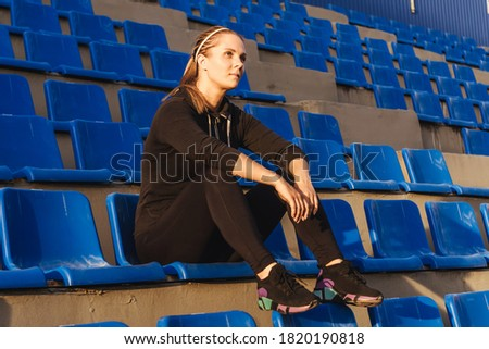 Fitness woman in black tracksuit sitting on the podium of the stadium. Woman after training. Sunset light, full length. Royalty-Free Stock Photo #1820190818